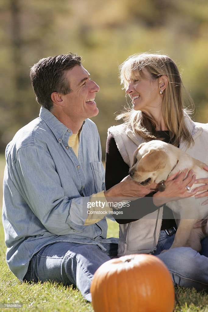 Couple playing with dog : Stockfoto