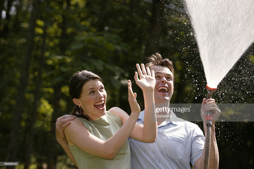 Couple playing with garden hose : Stockfoto