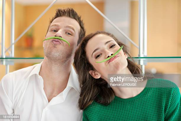 couple playing with green bean in the kitchen - cuisine humour photos et images de collection