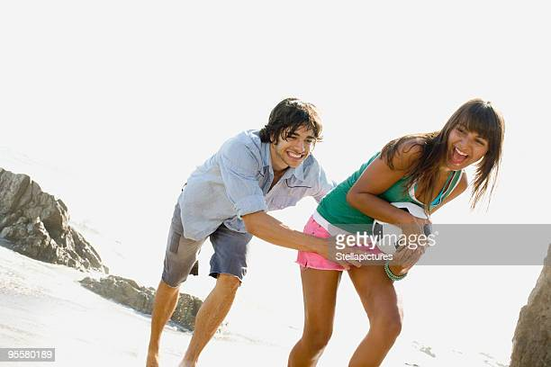 Couple playing with soccer ball on beach