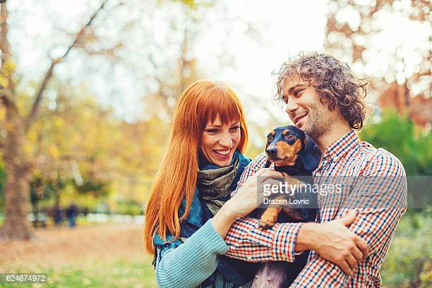 Couple playing with their dachshund dog