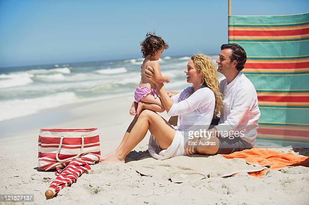 couple playing with their daughter on the beach - woman carrying tote bag stock photos and pictures