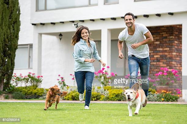 Couple playing with their dogs outdoors