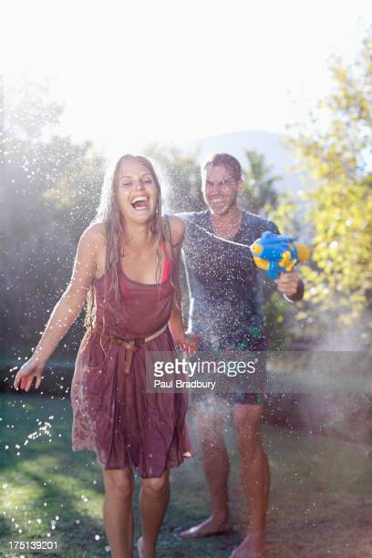 Paar spielt mit Wasser Waffen im Garten