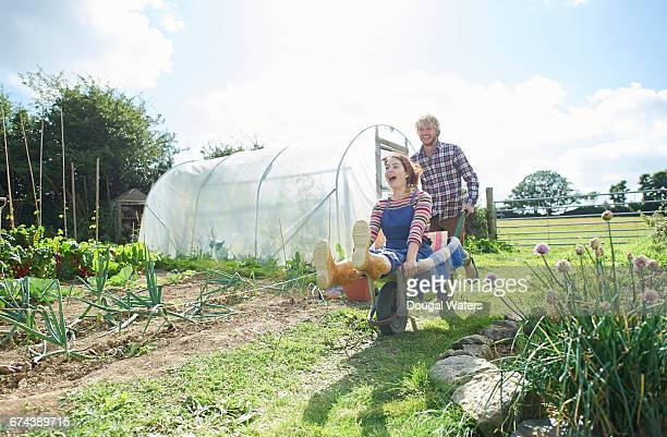 Couple playing with wheelbarrow on allotment.