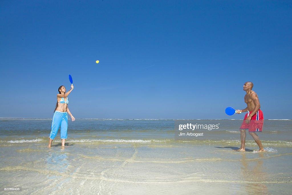 Couple plays paddle ball on beach : Stock Photo