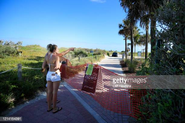 A couple point past a closure sign into South Pointe Park on the boardwalk in the South of Fifth neighborhood on March 22 2020 in Miami Beach Florida...