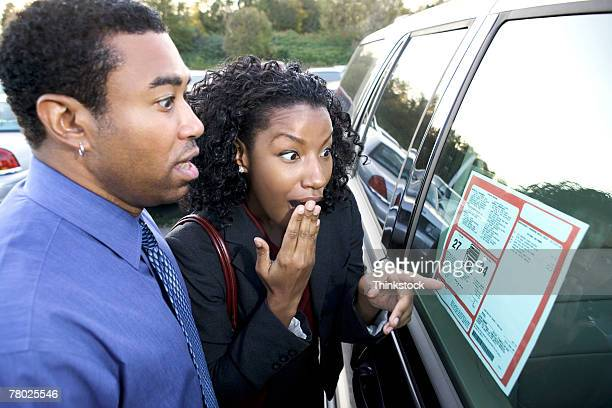A couple points and is shocked at the sticker price of a new car in the car lot