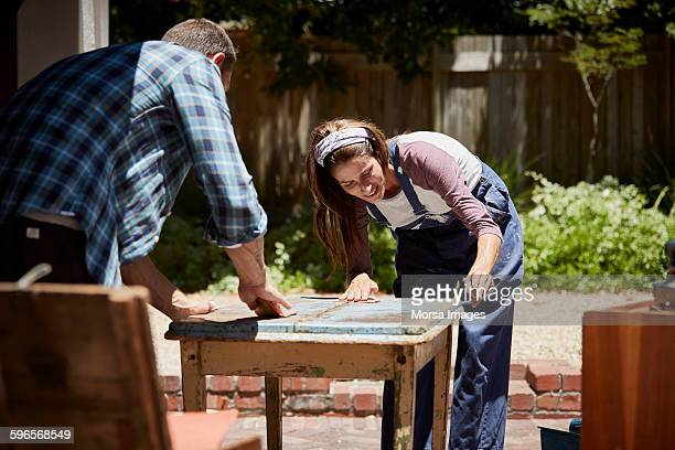 Couple polishing furniture outside house