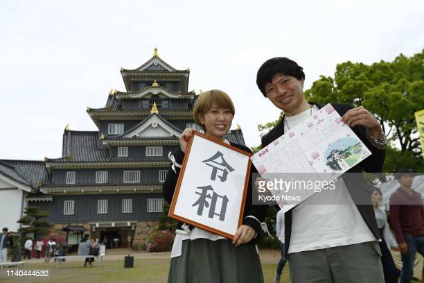A couple pose for a photo against the backdrop of Okayama Castle in western Japan after registering their marriage there on May 1 the first day of...