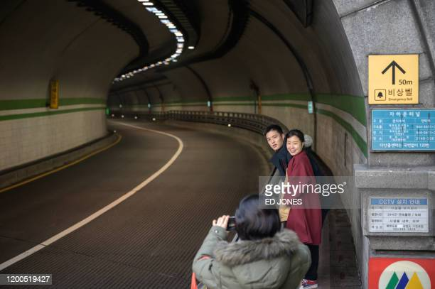 A couple pose for a photo at a tunnel featured in South Korean film 'Parasite' in Seoul on February 13 2020 Locations featured in the South Korea's...