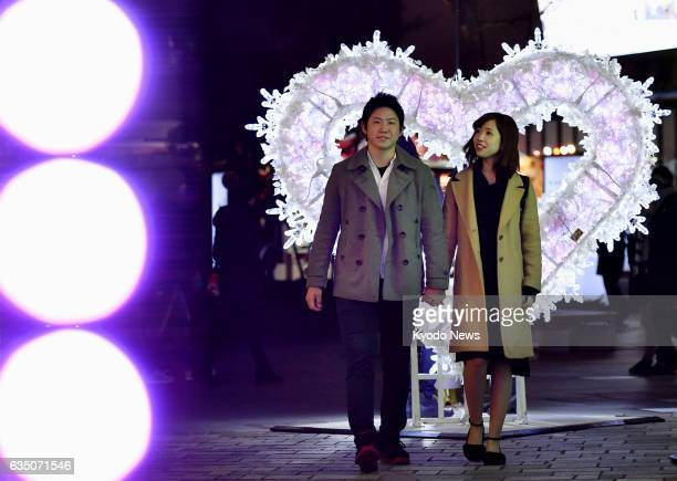 A couple pose for a photo in Tokyo on Feb 13 prior to Valentine's Day The woman said 'I'll give him chocolates tomorrow'