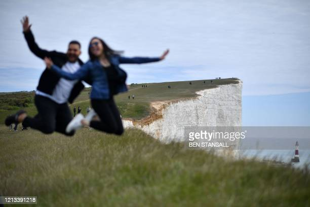 Couple pose for a photograph on the cliff-edge above the lighthouse at Beachy Head near Eastbourne on the south coast of England on May 17 following...