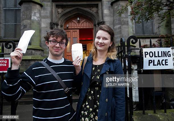 A couple pose for pictures with their voting slips at a polling station in the south of Edinburgh Scotland on September 18 during a referendum on...