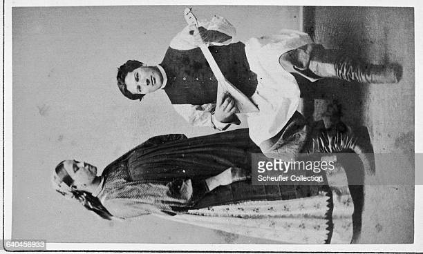 A couple pose in a studio as the man plays a traditional song of love on the balalaika to the pregnant woman Russia ca 18651875