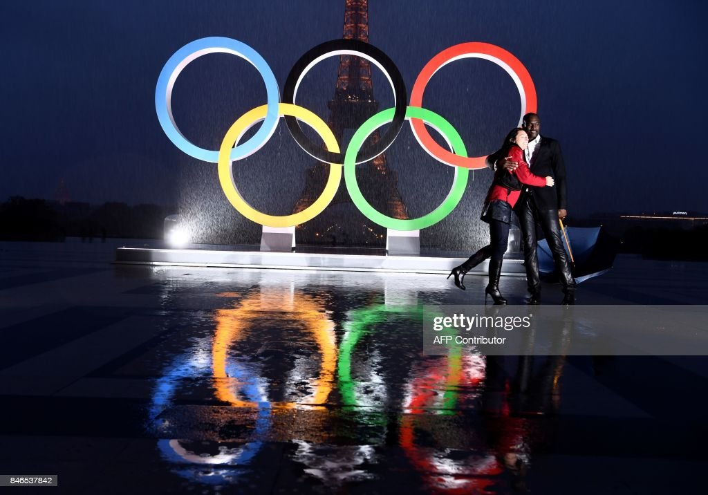 A couple pose in the rain beside the Olympics Rings on the Trocadero Esplanade near the Eiffel Tower in Paris, on September 13, 2017, after the International Olympic Committee named Paris host city of the 2024 Summer Olympic Games. The International Olympic Committee named Paris and Los Angeles as hosts for the 2024 and 2028 Olympics on September 13, 2017, crowning two cities at the same time in a historic first for the embattled sports body. /
