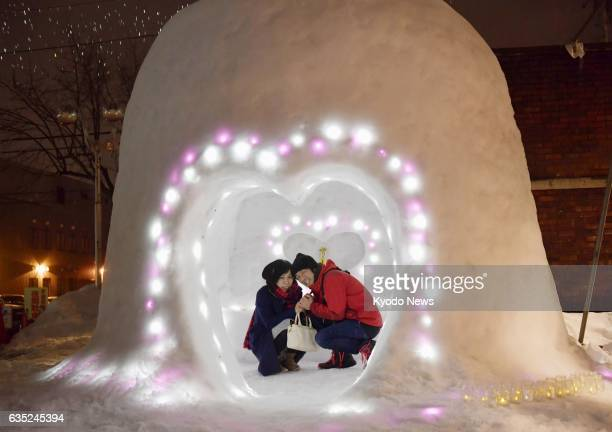 A couple pose inside a snow hut with a heartshaped entrance made especially for Valentine's Day at a square near the city office building in Yokote...