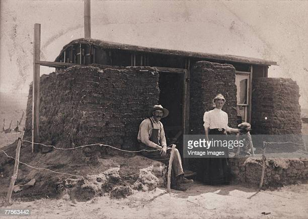 A couple pose with their dog outside their home which appears to be insulated with bricks of sod late 1800s or early 1900s