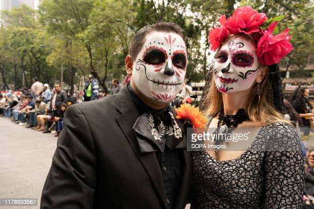 A couple pose with their faces painted before the procession begins during the Catrina Festival Thousands of people took to the streets of Mexico...