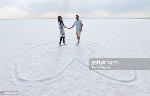 A couple poses for a photo in a heart shaped dried ground of Lake Salt which is the second largest lake in Ankara Turkey on July 18 2018 Lake Salt is...