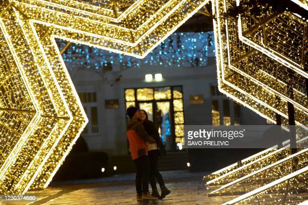 Couple poses for a picture at Podgorica's central square on the New Years' Eve on December 31 as gatherings and celebrations have been restricted...