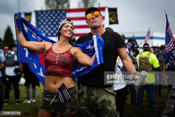 Couple poses for a portrait as several hundred members of the Proud Boys and other similar groups gathered for a rally at Delta Park in Portland,...