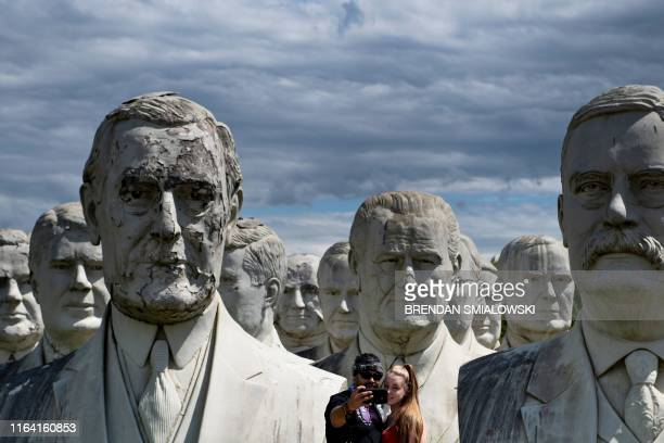TOPSHOT A couple poses for a selfie with giant salvaged busts of former US Presidents August 25 in Williamsburg Virginia Howard Hankins rescued the...