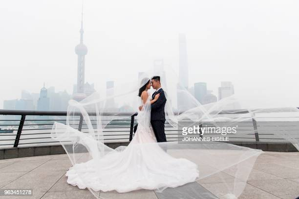 TOPSHOT A couple poses for a wedding photograper at the promenade on the Bund along the Huangpu River seen against the skyline of the Lujiazui...