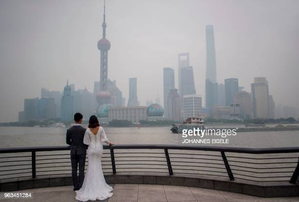 A couple poses for a wedding photograper at the promenade on the Bund along the Huangpu River seen against the skyline of the Lujiazui Financial...