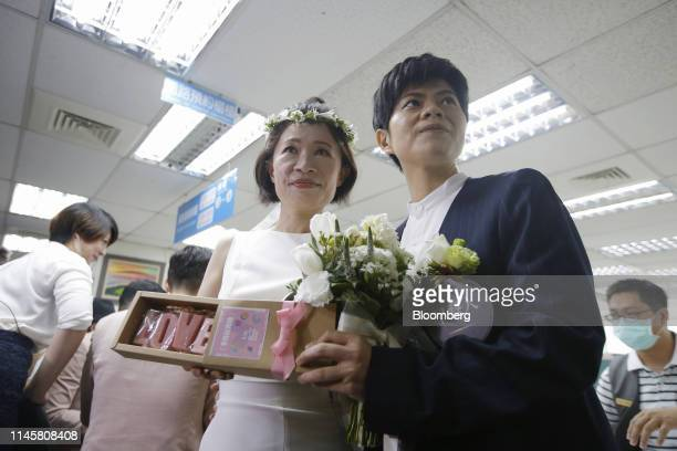 Couple poses for photographs while registering for marriage at a Household Registration Office in Taipei, Taiwan, on Friday, May 24, 2019. Same-sex...