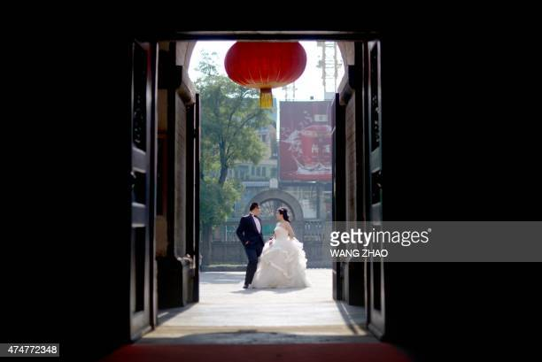 A couple poses for their wedding photos outside a church in Beijing on May 26 2015 AFP PHOTO / WANG ZHAO / AFP / WANG ZHAO