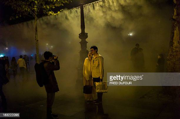 A couple poses next to an art installation by Japanese artist Fujiko Nakaya 'Fog Square' on October 5 at the Place de la Republique in Paris during...