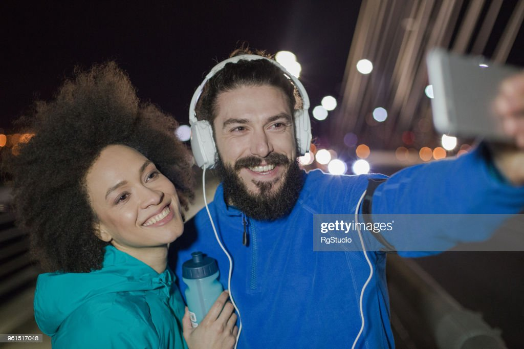 Couple Posing For A Selfie Outdoors At Night Stock Photo