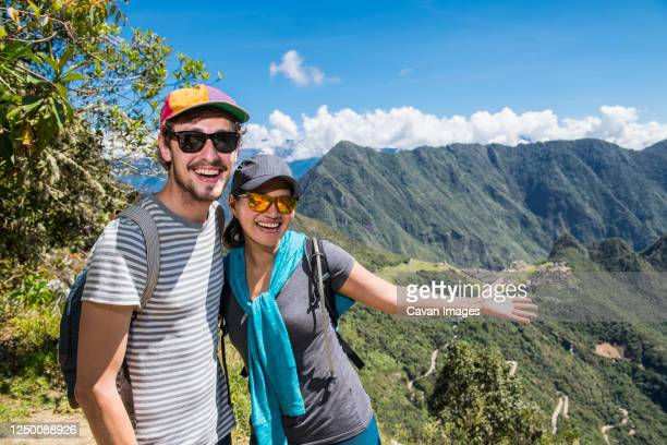 couple posing for camera on the inca trail close to machu picchu - mountain ridge stock pictures, royalty-free photos & images