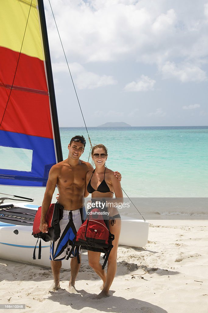 couple posing in front of their catamaran at a beach : Stock Photo