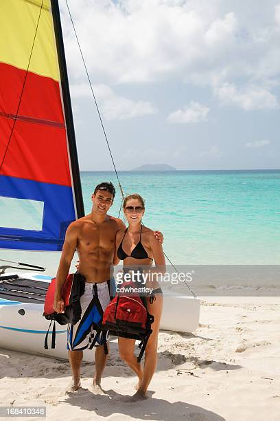 couple posing in front of their catamaran at a beach - catamaran sailing stock photos and pictures