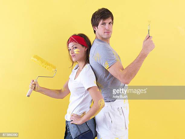 Couple posing in front of wall.