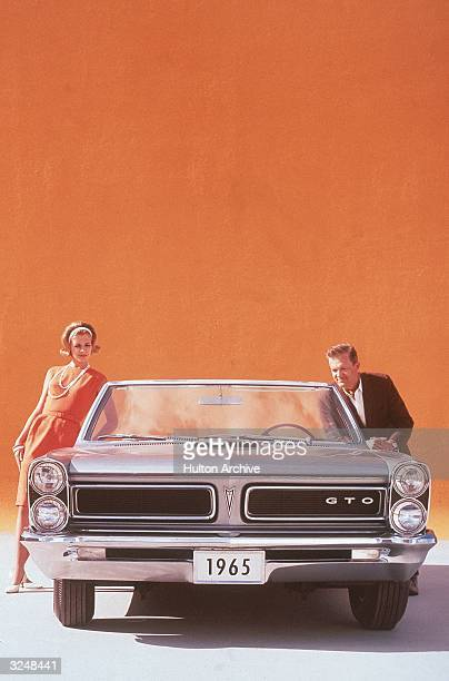A couple posing on either side of a silver 1965 Pontiac GTO convertible sports car in front of an orange backdrop
