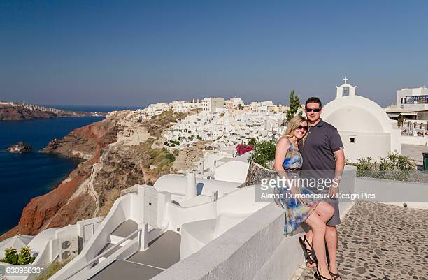 A couple posing together on a white wall on a greek island with the town in the background