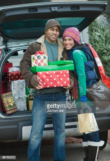 couple posing with christmas gifts by car - imagenes gratis fotografías e imágenes de stock