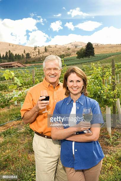 Couple posing with wine in vineyard