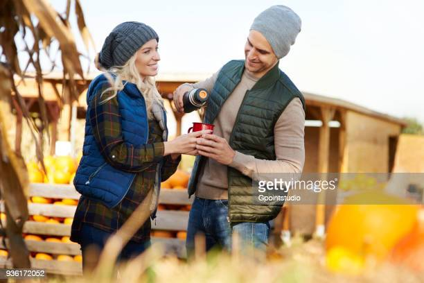 couple pouring coffee from flask at pumpkin patch - pumpkin patch stock photos and pictures