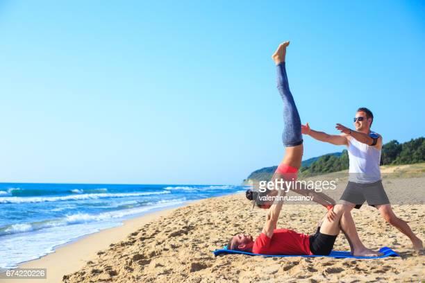 Couple practicing acroyoga  on beach
