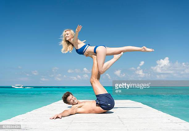 Couple practicing Acro-Yoga on Vacation