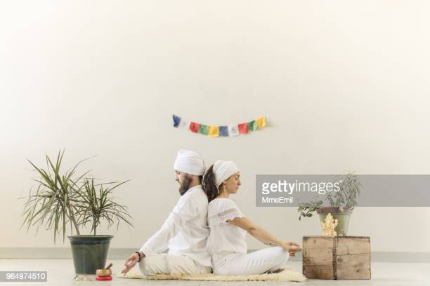 couple practicing kundalini yoga and meditating back to back - yogi stock photos and pictures