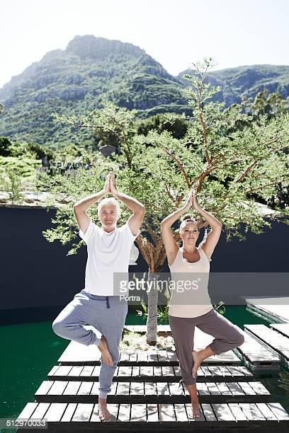 Couple practicing tree pose on boardwalk