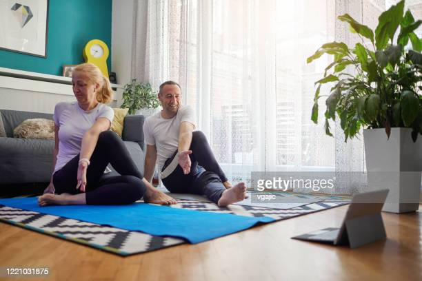 couple practicing yoga at home with online classes - practicing stock pictures, royalty-free photos & images
