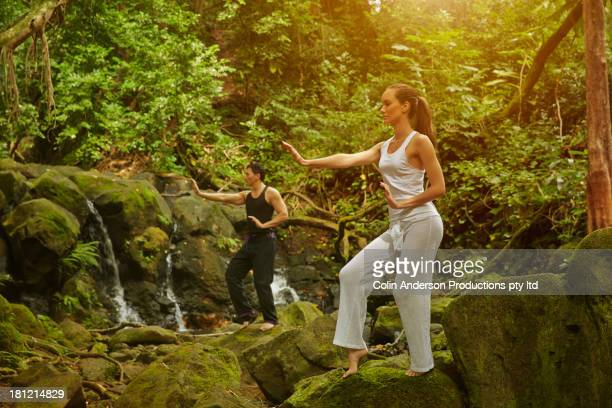 Couple practicing yoga in jungle