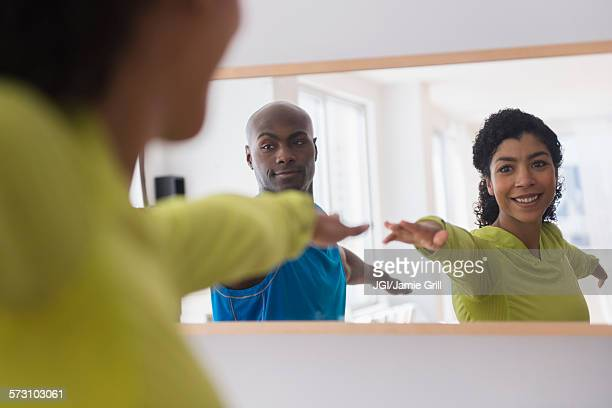 Couple practicing yoga in mirror