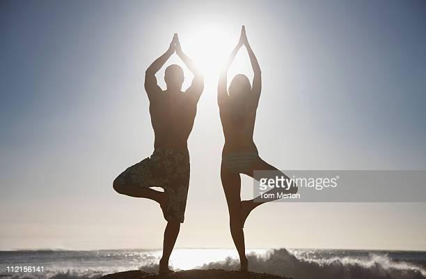 Couple pratiquant le yoga sur la plage